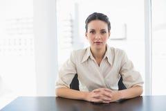 Femme d'affaires élégante sérieuse de brune regardant l'appareil-photo et joignant ses mains Image stock
