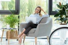 femme d'affaires élégante sûre travaillant sur l'ordinateur portable tout en se reposant dans le fauteuil Image libre de droits
