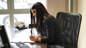 Femme d'affaires élégante s'asseyant à son fonctionnement de bureau Photographie stock