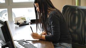Femme d'affaires élégante s'asseyant à son fonctionnement de bureau Photos libres de droits