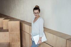 Femme d'affaires élégante tenant l'ordinateur portable dans le bureau moderne Photographie stock
