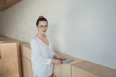 Femme d'affaires élégante tenant l'ordinateur portable tout en se tenant dans le bureau moderne Photo libre de droits
