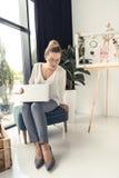 Femme d'affaires élégante travaillant avec l'ordinateur portable tout en se reposant dans le bureau moderne Photographie stock libre de droits
