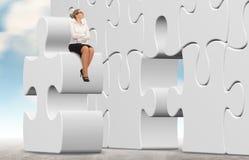 Femme d'affaires établissant un puzzle sur un fond de ciel Photographie stock libre de droits