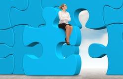 Femme d'affaires établissant un puzzle sur un fond de ciel Image stock
