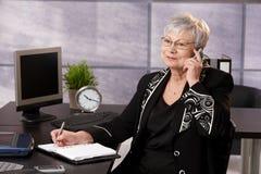 Femme d'affaires aînée à l'aide du portable photos stock
