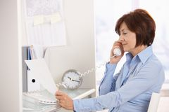 Femme d'affaires aînée sur le papier du relevé d'appel téléphonique. photographie stock