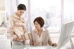 Femme d'affaires aînée travaillant avec l'aide Images stock