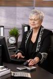 Femme d'affaires aînée travaillant dans le bureau Images libres de droits
