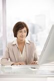 Femme d'affaires aînée travaillant sur l'ordinateur Photos stock