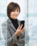 Femme d'affaires aînée utilisant le mobile images libres de droits