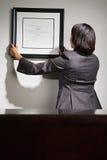 Femme d'affaires accrochant le certificat encadré image libre de droits