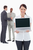 Femme d'affaires affichant l'ordinateur portatif avec des collègues images libres de droits