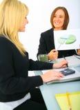 Femme d'affaires affichant le diagramme circulaire au collègue Image stock