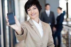 Femme d'affaires affichant le téléphone intelligent Image stock