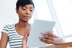 Femme d'affaires africaine attirante à l'aide de la tablette dans le bureau Photos stock