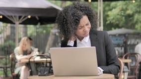 Femme d'affaires africaine avec douleur cervicale utilisant l'ordinateur portable extérieur clips vidéos