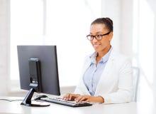 Femme d'affaires africaine avec l'ordinateur dans le bureau image libre de droits