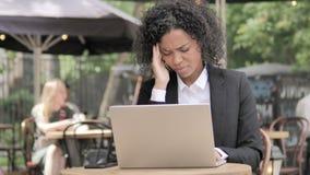 Femme d'affaires africaine avec le mal de tête utilisant l'ordinateur portable en café extérieur banque de vidéos