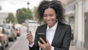Femme d'affaires africaine Cheering Success sur Smartphone se tenant extérieur sur le sentier piéton clips vidéos