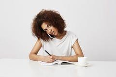 Femme d'affaires africaine parlant au téléphone sur le lieu de travail au-dessus du fond blanc Copiez l'espace Images libres de droits