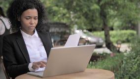 Femme d'affaires africaine Reading Contract et ordinateur portable d'utilisation en café extérieur banque de vidéos