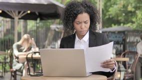 Femme d'affaires africaine Reading Documents tout en se reposant en café extérieur banque de vidéos