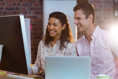 Femme d'affaires agissant l'un sur l'autre avec le collègue tout en travaillant sur l'ordinateur images stock