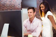 Femme d'affaires agissant l'un sur l'autre avec le collègue tout en travaillant sur l'ordinateur image libre de droits