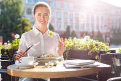 Femme d'affaires agréable appréciant la salade dans le restaurant Image stock
