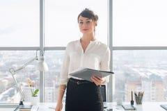 Femme d'affaires ambitieuse attirante se tenant dans le bureau moderne, tenant le dossier de papier, regardant l'appareil-photo,  Photographie stock