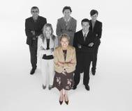 Femme d'affaires ambitieuse avec l'équipe de professionnels sur le fond blanc Images libres de droits