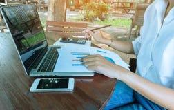 Femme d'affaires analysant le document de graphique financier avec le ton de vintage d'ordinateur portable et de téléphone portab images stock
