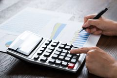 Femme d'affaires Analyzing Financial Report avec la calculatrice Image libre de droits