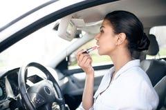 Femme d'affaires appliquant le rouge à lèvres sur des lèvres dans la voiture Photo libre de droits