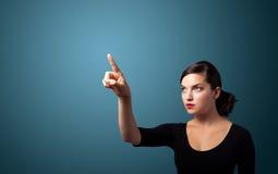 Femme d'affaires appuyant sur un bouton imaginaire photo libre de droits