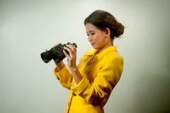 Femme d'affaires asiatique assez jeune dans le costume jaune tenant des jumelles. Photographie stock