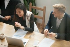 Femme d'affaires asiatique attirante et laughin caucasien d'homme d'affaires images stock