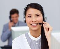 Femme d'affaires asiatique avec l'écouteur en fonction à son bureau Photographie stock libre de droits