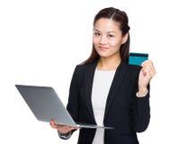 Femme d'affaires asiatique avec la carte de crédit d'ordinateur portable Photos stock