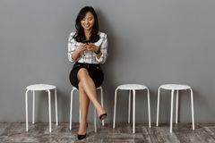 femme d'affaires asiatique de sourire avec l'attente de smartphone photographie stock