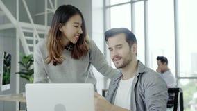 Femme d'affaires asiatique donnant le café à son collègue qui travaille avec l'ordinateur portable au bureau banque de vidéos