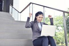 Femme d'affaires asiatique heureuse avec le fonctionnement d'ordinateur portable Images stock