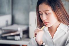 Femme d'affaires asiatique pensant avec le crayon et regardant vers le bas pour enrouler Photographie stock libre de droits