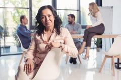 Femme d'affaires asiatique s'asseyant au bureau et regardant l'appareil-photo image stock