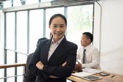 Femme d'affaires asiatique souriant à l'appareil-photo tandis que les collègues ont le rassemblement photo stock