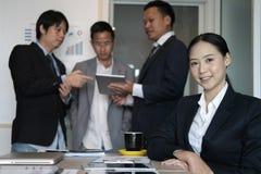 Femme d'affaires asiatique souriant à l'appareil-photo tandis que les collègues ont le rassemblement photographie stock libre de droits