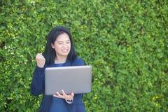 Femme d'affaires asiatique tenant le carnet d'ordinateur et montrant le pouce composant le geste correct photos libres de droits
