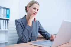 Femme d'affaires assez blonde à l'aide de son ordinateur portable Photo libre de droits