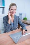Femme d'affaires assez blonde téléphonant et à l'aide de son ordinateur portable Image stock
